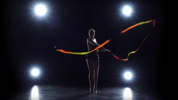 Flexible gymnast with tape creates beautiful hands graceful movements.Black background. Light rear. Slow motion