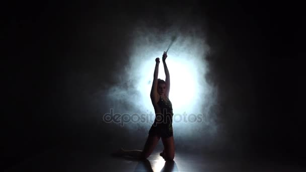 Gymnast with mace doing acrobatic moves. Black background. Slow motion. Silhouette