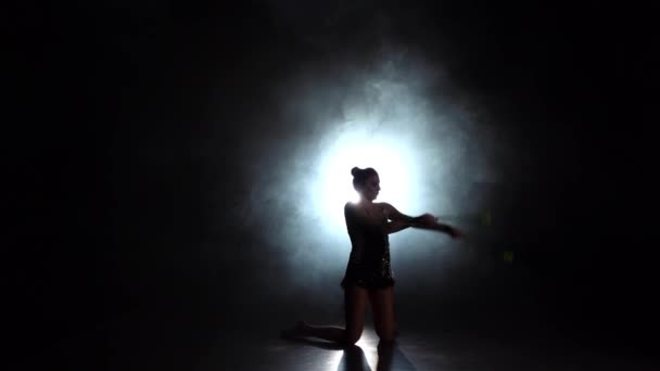 Rhythmic gymnast throws mace up and catches her. Black background. Light rear. Silhouette. Slow motion