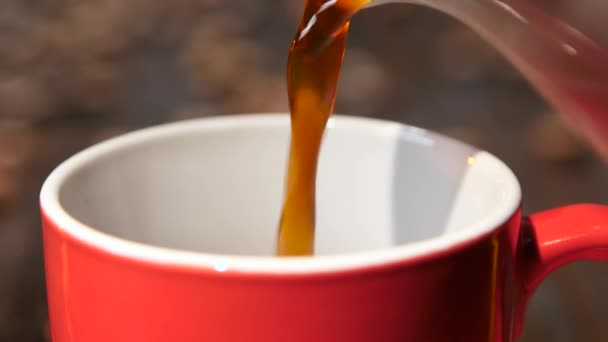 Closeup. Black coffee poured from coffeepot in red small cup