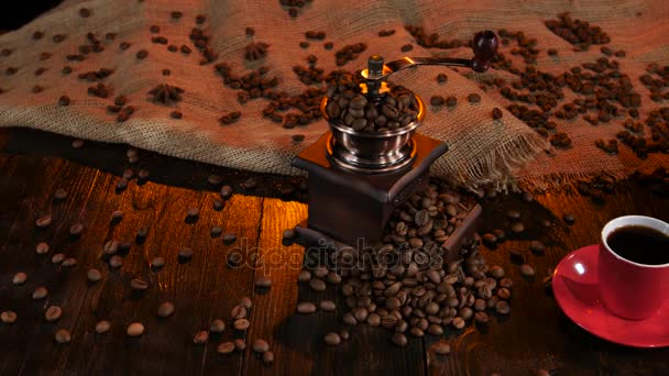 Coffee grinder full of coffee beans and cup of espresso