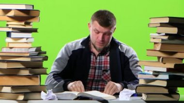 Man sitting at his desk writes his notebook information. Green screen
