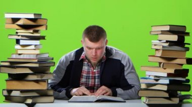 Man sitting at the table reading, finding information and happy. Green screen