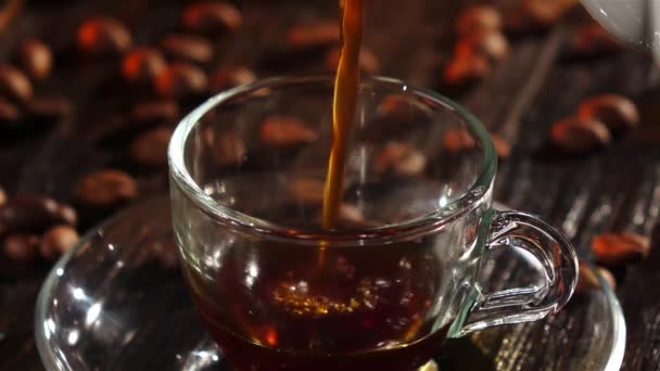 Black coffee is poured into a glass transparent cup. Closeup