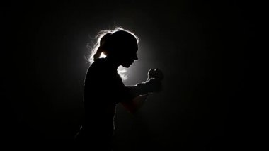 Woman boxer preparing for a competition. Slow motion. Black background. Side view. Silhouette