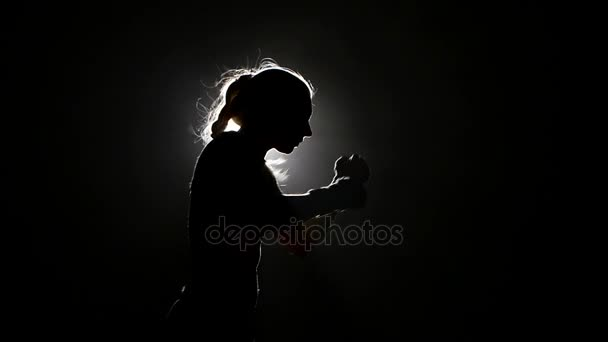 Žena boxer přípravě na soutěž. Zpomalený pohyb. Černé pozadí. Boční pohled. Silueta