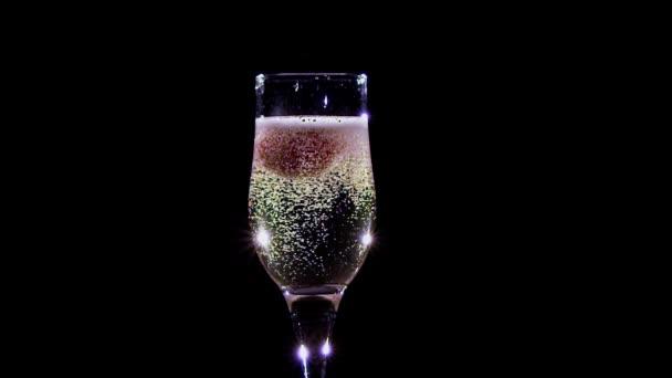 Erdbeere im Glas mit Champagner überzogenen Blasen. Zeitlupe