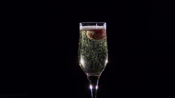 Lassú mozgás. Érett eper a pohár pezsgő pezsgő