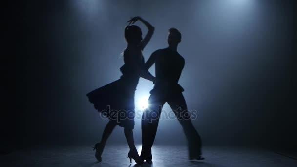 Profesionální pár jive tanečníků pózuje v zakouřené studio silueta