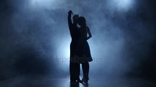 Professional couple of tango dancers posing in smoky studio, silhouette