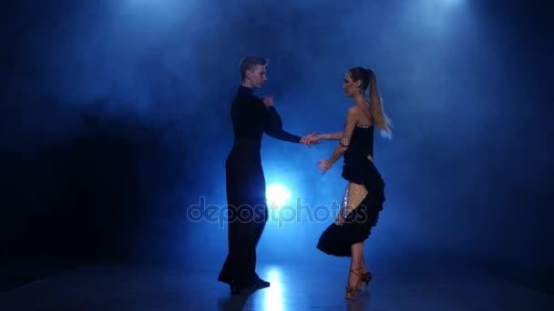 Happy couple dancing jive in smoky studio with blue spotlight