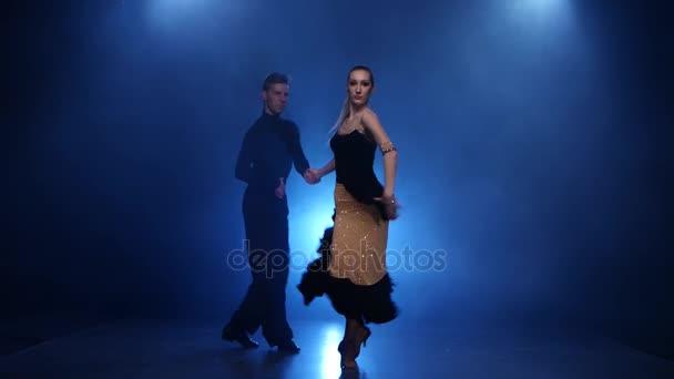 Happy couple dancing samba in smoky studio with blue spotlight