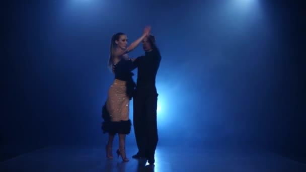 glückliches Paar tanzt Rumba im verrauchten Studio mit blauem Scheinwerfer