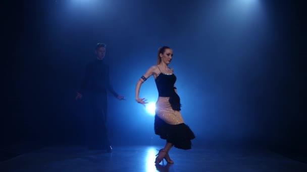 Happy couple dancing latino in smoky studio with blue spotlight