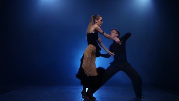 Salsa dancing pair of professional elegant dancers in smoky studio