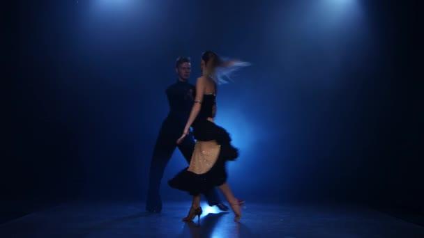 Rumba dancing pair of professional elegant dancers in smoky studio