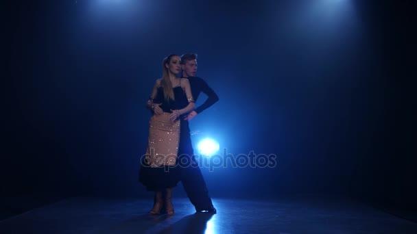 Jive dancing pair of professional elegant dancers in smoky studio