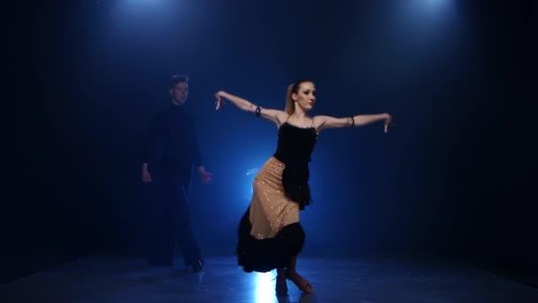 Latinamerican dancing pair of professional elegant dancers in smoky studio