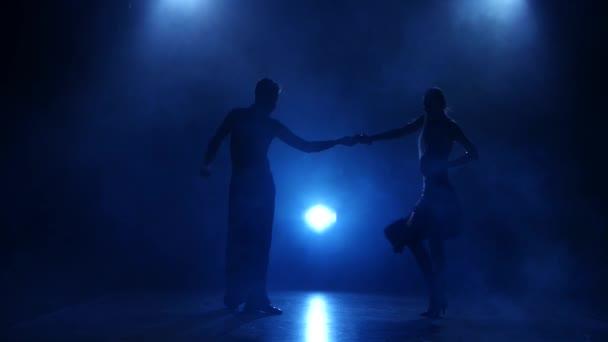 Silhouette of pair dancers performing samba dance in smoky studio