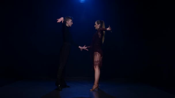 Contemporary dancing pair of professional elegant dancers in smoky studio