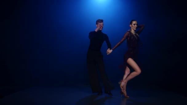 Rumba dancing couple of professional elegant dancers in smoky studio