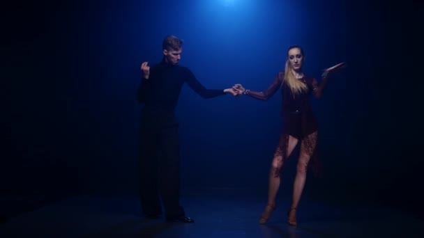 Tango dancing couple of professional elegant dancers on blue background
