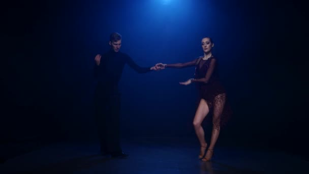 Salsa dancing couple of professional elegant dancers on blue background