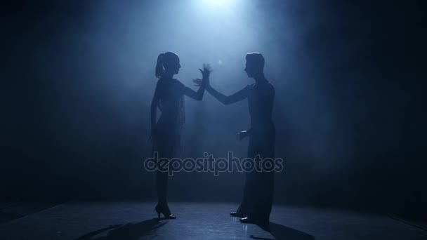 Dance element from the rumba, silhouette couple ballroom. Black background