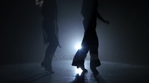 Dance couple demonstrating magnificent choreography of quickstep, black background. Close-ups