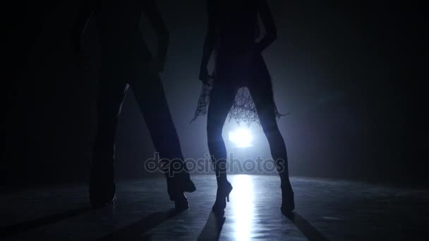Dance couple demonstrating magnificent choreography of latino, black background. Close-ups