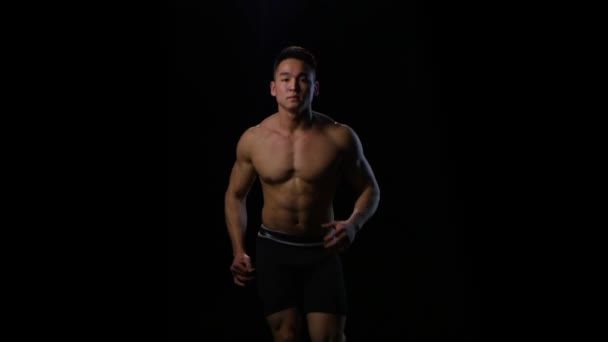 Athlete run on the black background at fast pace. Studio
