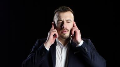 Podnikatel v černém obleku trpí bolestí hlavy a masáž