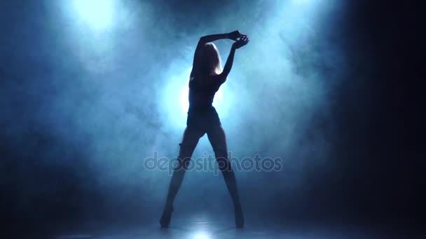 Szőke showgirl bőr fehérnemű táncok, füstös háttérben, lassú mozgás