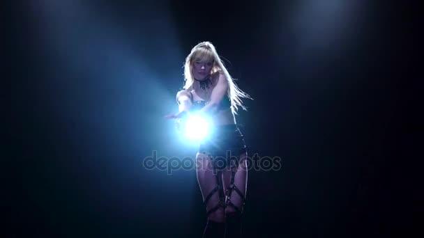 Blonde in leather lingerie dances in black studio. Slow motion
