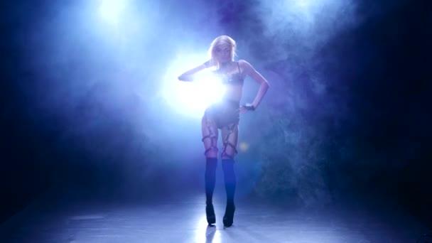Sexy dancer demonstrating her perfect sensual figure in smoky studio