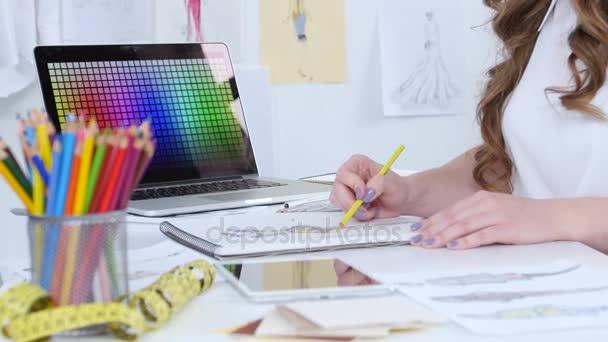 Umělec sedí ve své studii, načrtne nové kolekce. Detailní záběr