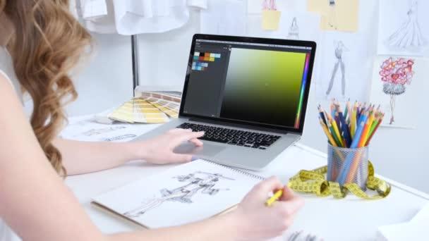Návrhář se dívá na počítač a vybere odstíny pro novou kolekci oblečení