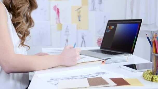 Umělec se dívá na počítač a vybere odstíny pro novou kolekci oblečení