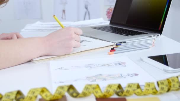 Módní návrhář kreslí náčrty pro novou kolekci a dívá na počítači