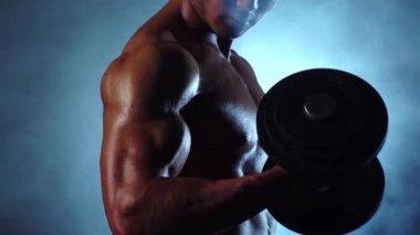 Asian weightlifter training biceps with a dumbbells. Black smoke background. Slow motion