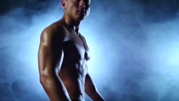 Ázsiai izmos ember mutatja be a testét, erőt és kitartást. Fekete füst háttér. Lassú mozgás