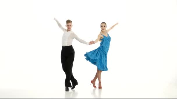 Pair of professional dancers perform samba on white studio background