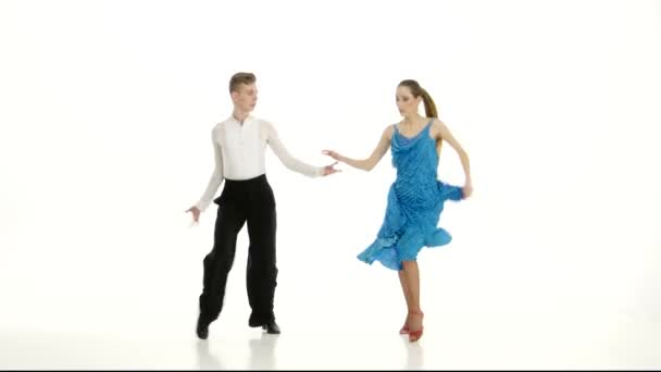 Pair of professional dancers perform salsa on white studio background