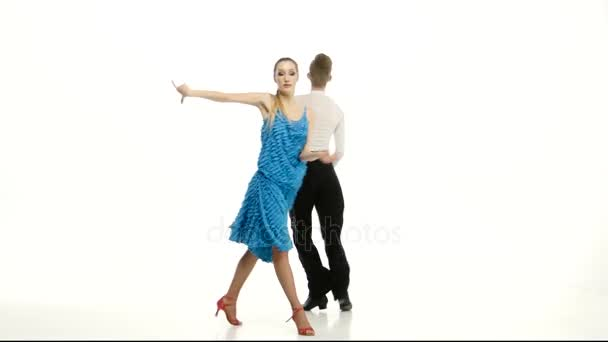 Couple of graceful dancers perform salsa on white studio background