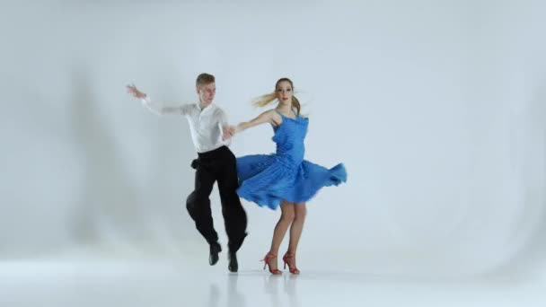 Couple of graceful dancers perform ballroom on white background, shadow