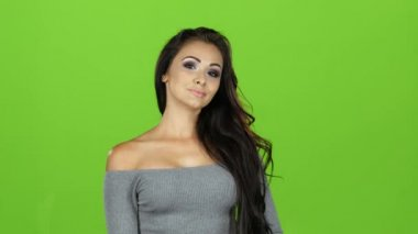 Brunette girl in sweater applauding looking at camera, green screen