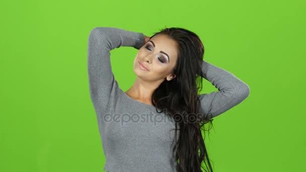 Barna nő pózol a kamera, zöld képernyő szürke pulóver