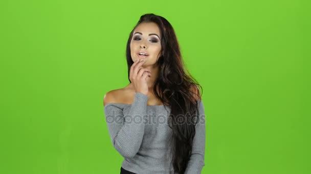 Sexy model bruneta žena pošle vzduch Polibky, zelené pozadí
