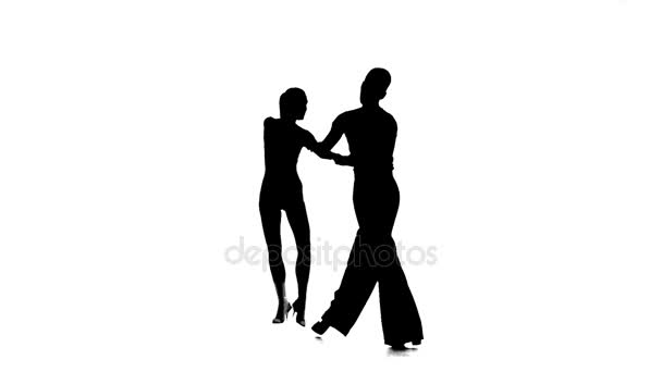 Silhouette pair dancers perform ballroom dance, white background, slow motion