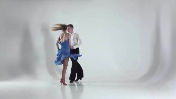 Pár je tanec samba na bílém pozadí, stín. Zpomalený pohyb